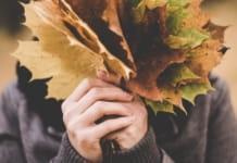 Vrouw verbergt haar gezicht achter herfstbladeren